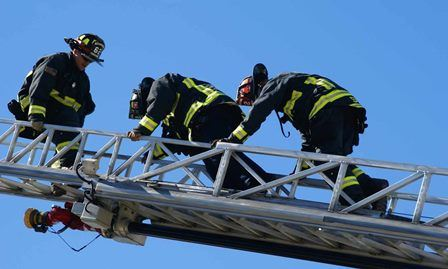Firefighters climbing ladder from fire apparatus