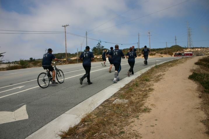 Group of officers running up a hill and one officer on a bike