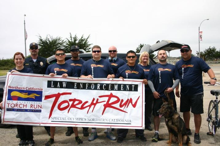 Group of officers and canine standing behind torch run banner