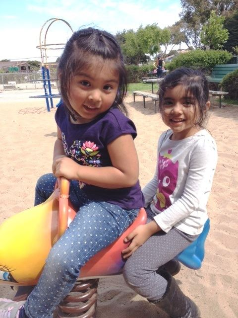 Two young girls on dolphin playground equipment