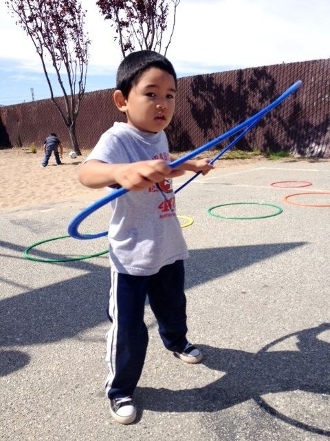 Young boy using a blue hula hoop