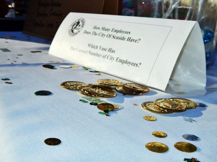"View of table with plastic coins and a sign stating ""Guess the Number of City of Seaside Employees"""
