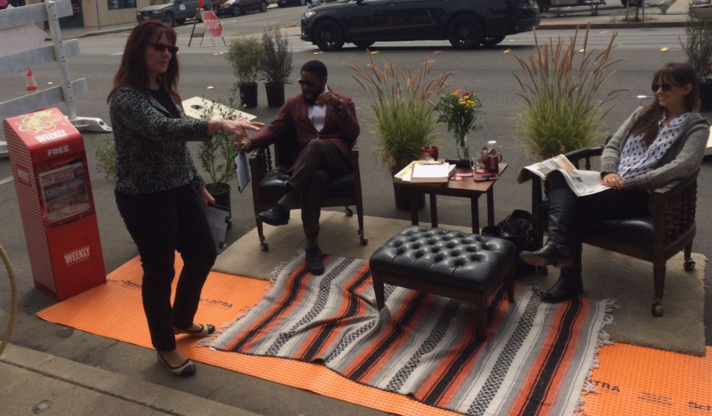 Three people, chairs, table and rug outside at Park(ing) day