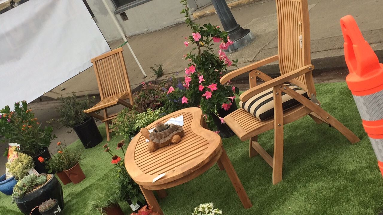 Wooden table and chairs set up at spot at Park(ing) day