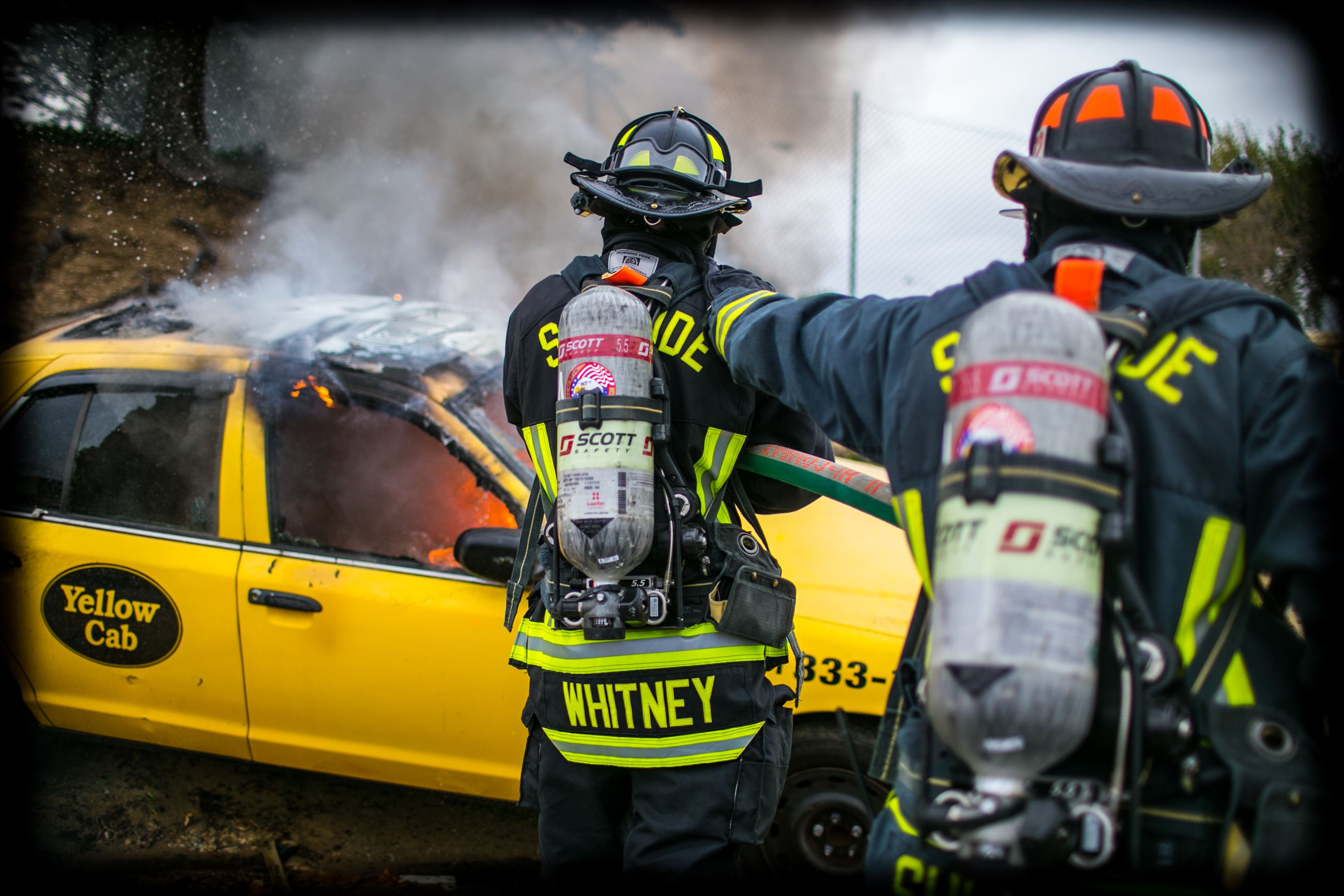 Two FD personnel in turnout gear extinguishing a burning yellow cab