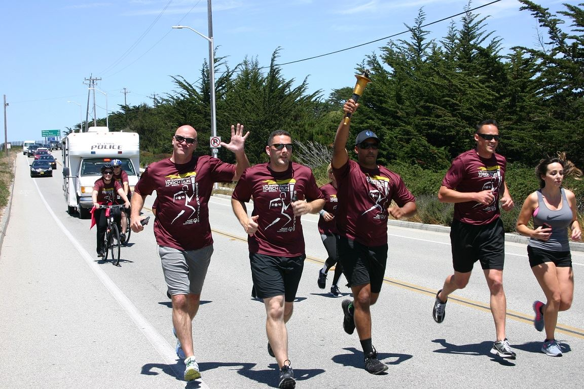 Group of Torch Run participants running along road