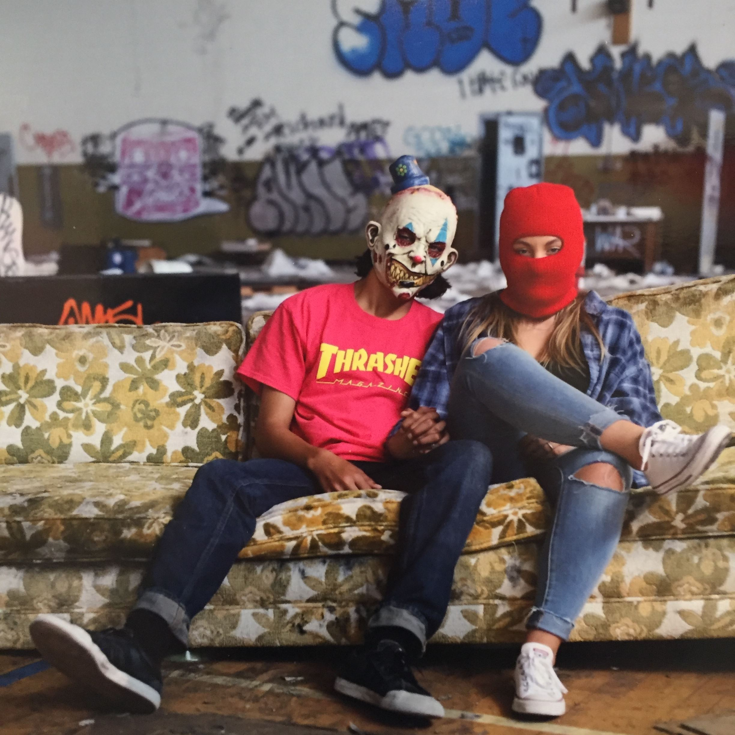 Photograph of two masked people on couch surrounded by graffiti