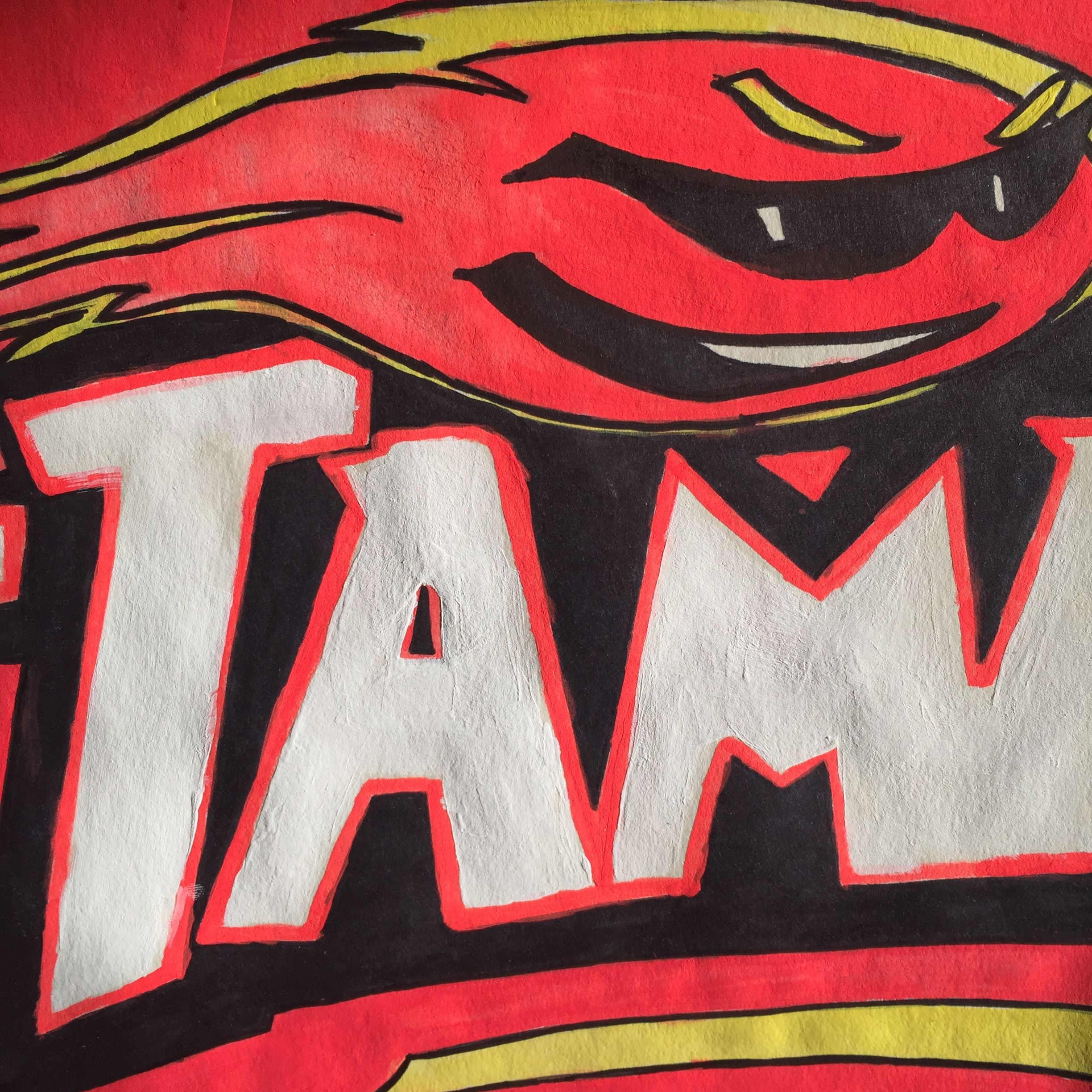 Red, black and white painting of the letters T.A.M