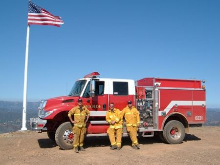 Three firefighters standing in front of fire engine by an American Flag