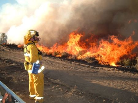 Firefighter in gear standing in front of flames at Patterson Canyon Burn