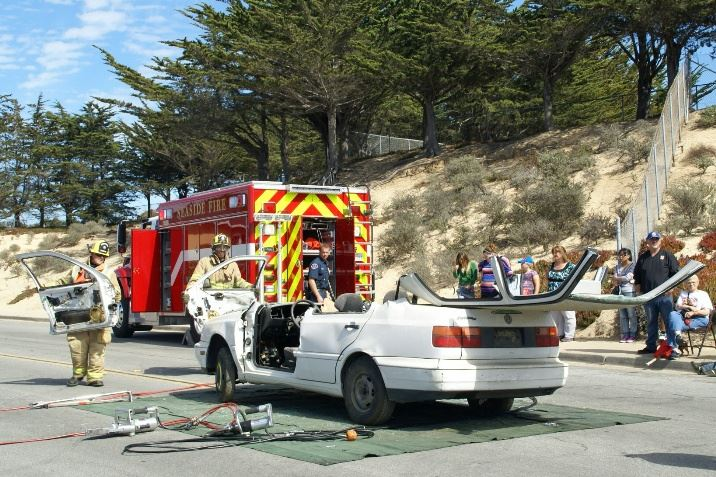 Firefighter utilizing extrication tools on white vehicle in front of rescue engine during Open House demonstration