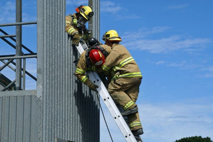 Three firefighters demonstrating a ladder rescue from the training ladder