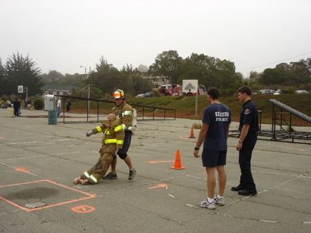 Two firefighters observing a firefighter carrying a training dummy during physical agility test