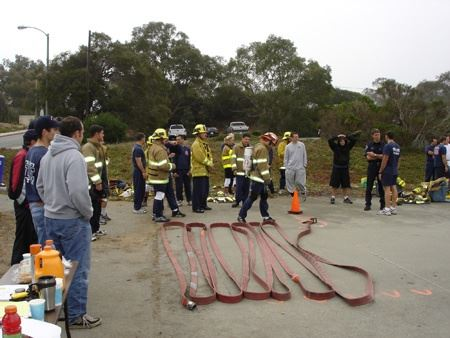 Group of firefighters preparing fire hose during physical agility test
