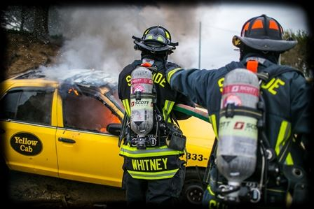 Two firefighters extinguishing a vehicle fire