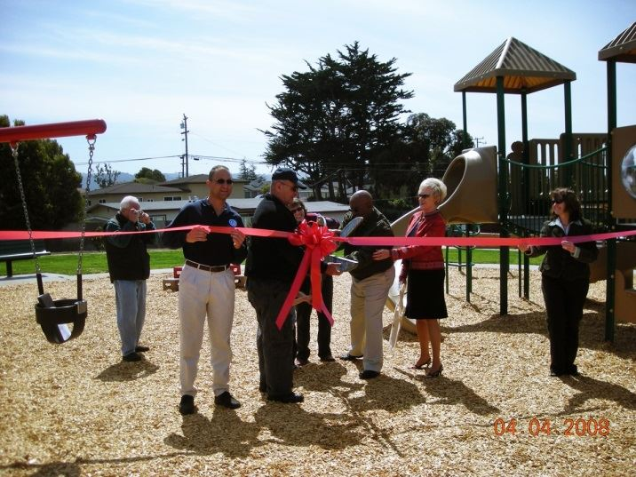 Red ribbon cut at park opening by Council Members